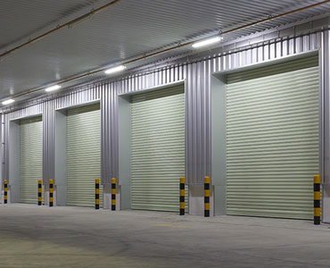 Exterior of factory with shutter door night time.